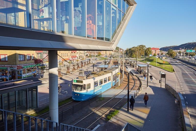 Mölndal station med en spårvagn och människor